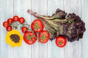 ovanifrån av grönsaker som tomatbasilika med skål med svartpepparfrön på träbakgrund foto
