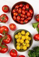 ovanifrån av grönsaker som koriander tomat spenat med skålar av tomater på trä bakgrund foto
