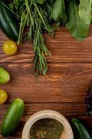 ovanifrån av grönsaker som gurka tomat mynta spenat med svartpeppar på trä bakgrund foto
