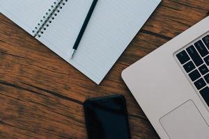 anteckningsbok och dator på brunt trägolv foto