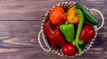 ovanifrån av grönsaker som gurka peppar tomat i korg på trä bakgrund med kopia utrymme