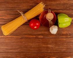 ovanifrån av spagetti pasta med tomat vitlökpeppar och smält smör på trä bakgrund med kopia utrymme foto
