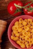 ovanifrån av rör-rigat pasta i skål med tomater och salt på träbakgrund