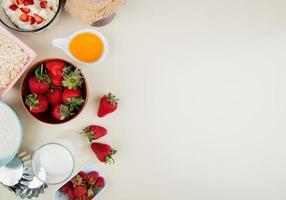 ovanifrån av jordgubbar i skål med keso smör mjölk havre på vänster sida och vit bakgrund med kopia utrymme foto