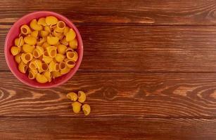 ovanifrån av rör-rigate pasta i skål på trä bakgrund med kopia utrymme foto