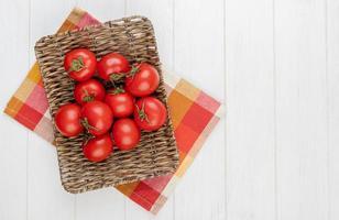 ovanifrån av tomater i korgplatta på rutigt tyg på vänster sida och träbakgrund med kopieringsutrymme