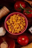 ovanifrån av rör-rigat pasta i skål med salt tomatsmör på träbakgrund