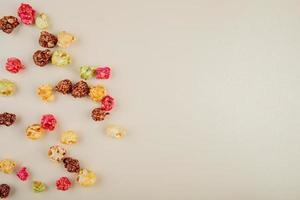 ovanifrån av skittles popcorn på vänster sida och vit bakgrund med kopieringsutrymme
