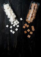ovanifrån av vita och bruna sockerbitar utspridda från glasburkar på mörk träbakgrund med kopieringsutrymme