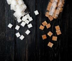 ovanifrån av vita och bruna sockerbitar utspridda från glasburkar på mörk träbakgrund