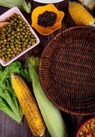ovanifrån av liktornar med gröna ärtor svartpeppar och sallad på träbakgrund foto