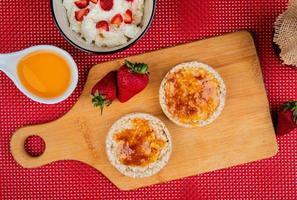 ovanifrån av krispiga knäckebröd smorda med sylt och jordgubbar på skärbräda med havregryn och smält smör på röd och vit bakgrund foto