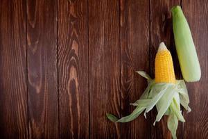 ovanifrån av majskolvar med skal på träbakgrund med kopieringsutrymme foto