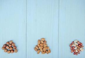 ovanifrån av blandad av nötter hög isolerad på blå bakgrund mandlar hasselnötter och jordnötter med kopia utrymme foto