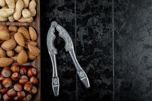 ovanifrån av nötblandning hasselnötter mandel och jordnötter i skal med nötter smällare på svart bakgrund med kopia utrymme
