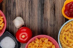 ovanifrån av makaroner som rotini pipe-rigate och andra i skålar med ketchup salt vitlök tomat på trä bakgrund foto