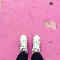 person som bär vita sneakers som står på rosa golv foto