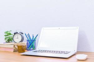 bärbar dator och andra föremål på skrivbordet foto