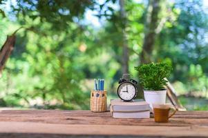 böcker och väckarklocka på skrivbordet