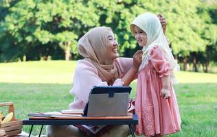 muslimska mödrar och döttrar njuter av sin semester i parken. kärlek och band mellan mor och barn
