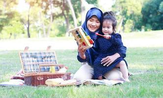 muslimska mödrar och döttrar njuter av sin semester i parken. kärlek och band mellan mor och barn foto