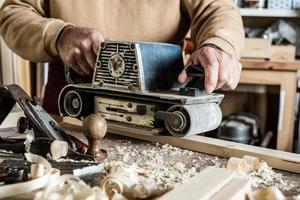 elektrisk bandslipmaskin, slipmaskin i manlig hand. bearbetning av arbetsstycke på ljusbrunt träbord. sidovy, närbild foto