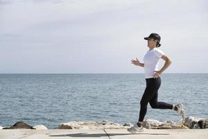 kvinna med mössa och solglasögon som springer längs strandpromenaden, havet i bakgrunden foto