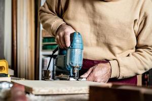 snickarens händer med elektrisk sticksåg närbild. arbeta i en snickarverkstad. en man skär plywood med en elektrisk sticksåg. elektrisk verktyg för träbearbetning. foto