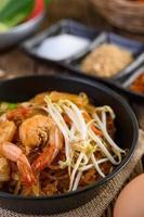 pad thai räkor i en svart panna med ägg och kryddor