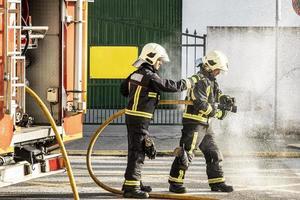 brandmän med en vattenslang som drar vatten för att släcka en brand