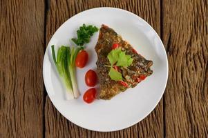 friterat fiskhuvud toppat med chili på en vit platta