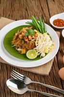pad thai med citron, ägg och kryddor på ett träbord