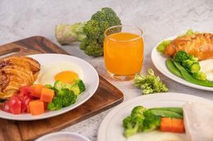 frukostspridning av kyckling, stekt ägg, broccoli, morötter, tomater och sallad