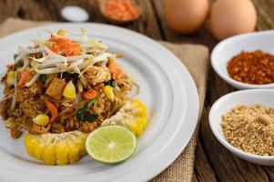 pad thai med citron, ägg och kryddor på ett träbord foto
