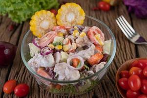 frukt- och grönsaksallad i en glasskål på träbord
