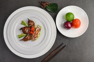 kryddig stekt havskatt på en vit platta med ätpinnar