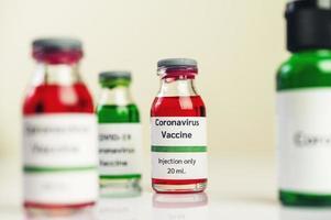 vaccinet mot covid-19 i röda och gröna flaskor