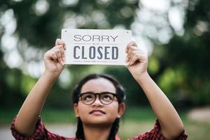 flicka som håller ett stängt tecken