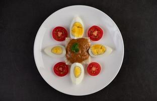 bröd toppad med chilipasta med kokta ägg och tomater