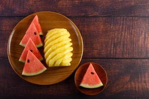 vattenmelon och ananasskivor på mörkt träbord