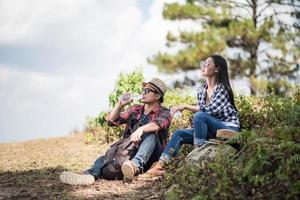 ungt par som tittar på kartan medan de vandrar i skogen foto