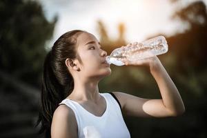ung fitness tonåring dricksvatten efter att ha kört träning foto