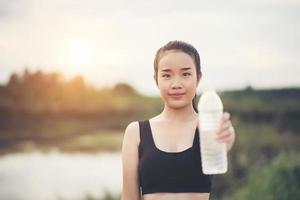ung fitness tonåring håller vattenflaska efter att ha kört träning foto