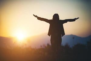 silhuett av kvinna över vacker solnedgång bakgrund foto