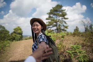 ungt par som går med ryggsäckar i skogen