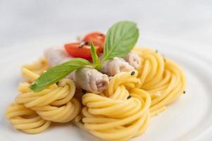 pläterad spagetti och fläsk ordnad på en vit platta