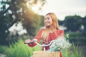 ung asiatisk kvinna som cyklar i en park