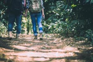 unga aktiva resenärer som håller hand medan de går i skogen foto