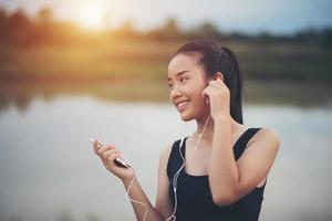 fitness tonåring med hörlurar lyssnar på musik under hennes träning foto