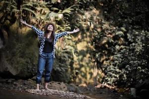 glad ung kvinna som lyfter armarna för att hälsa på solen i skogen